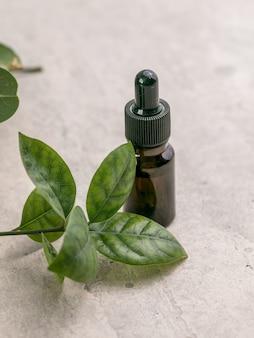 ダフネの葉とエッセンシャルベイローレルオイルのガラス瓶。健康的なライフスタイルスパ、セラピーのコンセプト。
