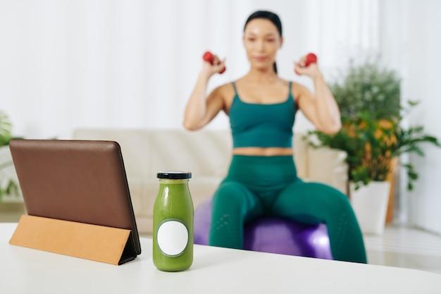 タブレットコンピューターの隣のテーブルに緑のスムージーのガラス瓶とバックグラウンドでダンベルで運動している女性に合う