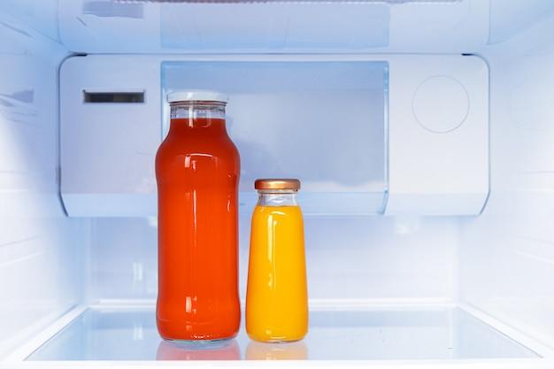 Стеклянная бутылка сока на полке холодильника