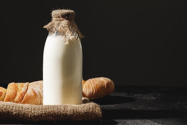 Стеклянная бутылка молока с нарезанным хлебом багетом