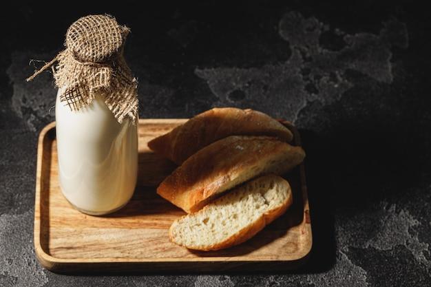 スライスしたバゲットパンと牛乳のガラス瓶