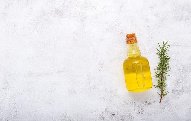 Стеклянная бутылка оливкового масла и ветвь розмарина на белом фоне бетона.