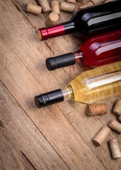 Стеклянная бутылка вина с пробками на деревянном столе