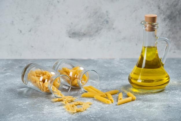 Una bottiglia di vetro di olio con maccheroni crudi.
