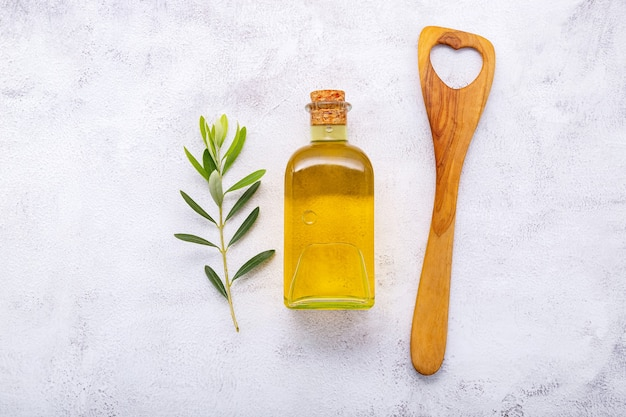Glass bottle of olive oil and olive branch set up on white concrete background.