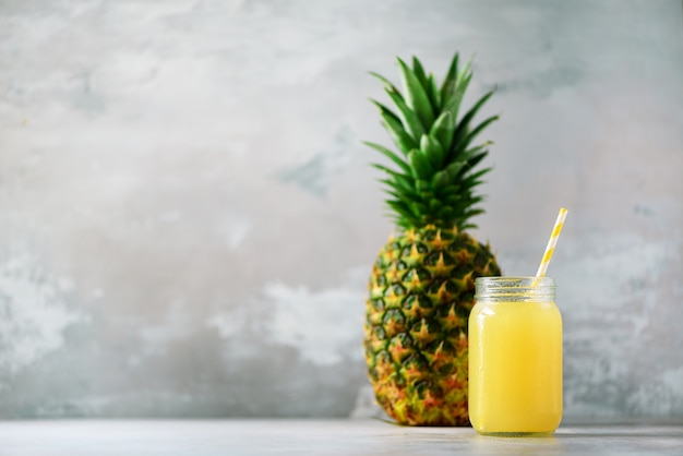 Glass bottle of pineapple juice and whole fruit. raw, vegan, vegetarian, clean eating diet.
