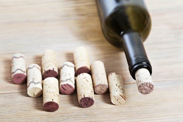 Glass bottle of red wine with corks on old wooden background.