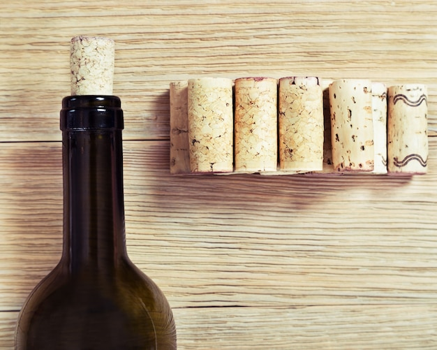Glass bottle of red wine with corks. on old wooden table. top view. soft focus. toned photo.