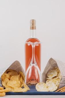 Vetro e bottiglia di vino rosato con vari snack sul tavolo bianco.