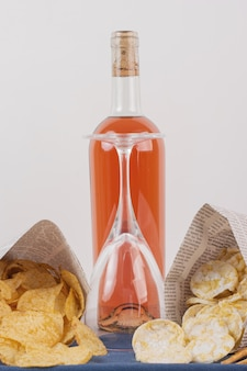 Glass and bottle of rose wine with various snack on white table.