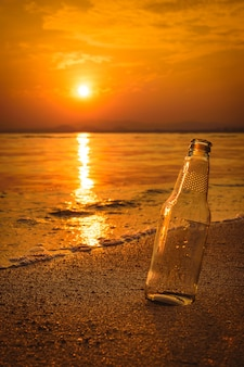 Glass bottle on the sand at sunset