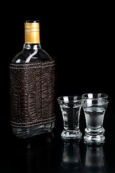 Glass bottle and shot of vodka on a black table