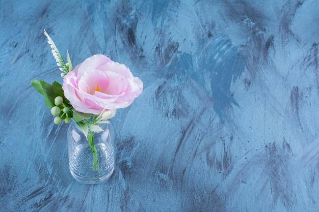 Bottiglia di vetro di singolo fiore rosa con foglie su blu.