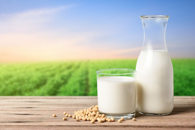 Glass and bottle of soy milk on wooden table with blur green soybean field background..