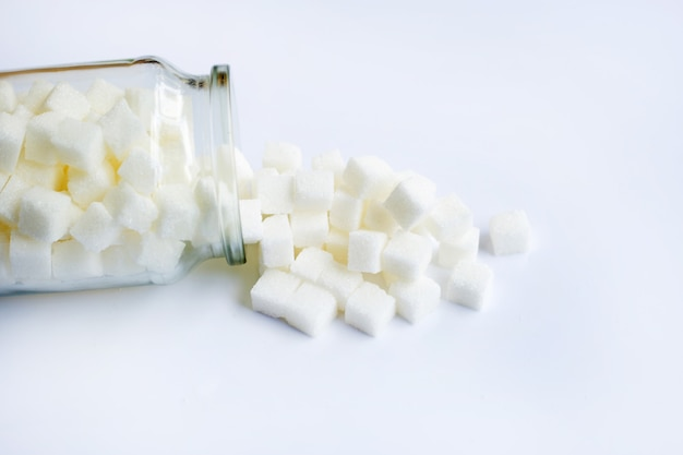 Glass bottle of sugar cubes on white