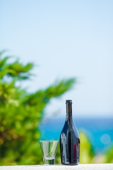 Glass and bottle of tasty red wine on balcony in greek island with view of sea