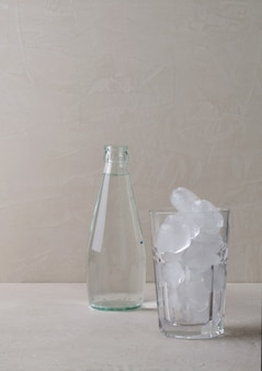 A glass bottle of water stands on a beige background. in a blurmeled focus glass with ice, copying space