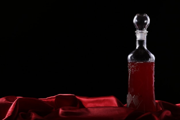 Glass and bottle of wine on a dark background silk