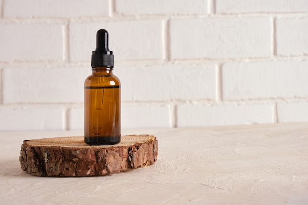 Стеклянная бутылка с пипеткой на спиле дерева на бежевом текстурированном фоне copy space
