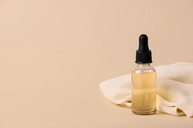 テキスタイルとベージュの背景に血清とピペットとガラス瓶。スキンケア美容製品のシルキーな質感。ビタミンで保湿する顔用の女性用化粧品。スペースをコピーします。