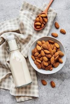 Glass bottle with almond milk and almonds on the table
