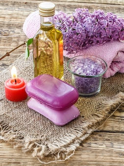 Glass bottle with aromatic oil, bowl with sea salt, soap, burning candle, lilac flowers and towel for bathroom procedures on old wooden boards. spa products and accessories. top view.