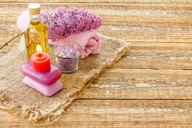 Glass bottle with aromatic oil, bowl with sea salt, soap, burning candle, lilac flowers and towel for bathroom procedures on wooden boards. spa products and accessories. top view.