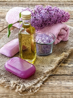 Glass bottle with aromatic oil, bowl with sea salt, soap, lilac flowers and towel for bathroom procedures on old wooden boards. spa products and accessories. top view.