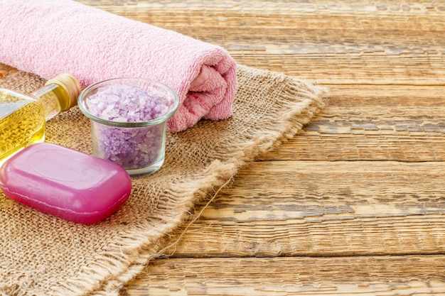 Glass bottle with aromatic oil, bowl with sea salt, soap and towel for bathroom procedures on wooden boards. spa products and accessories. top view.