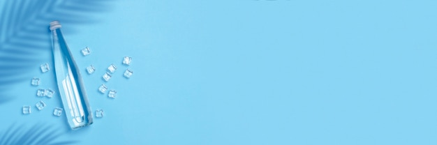 Стеклянная бутылка с чистой водой на синем пространстве с кубиками льда. понятие о здоровье и красоте, водный баланс, жажда, жара, лето. плоская планировка, вид сверху. баннер.
