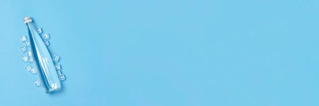 Стеклянная бутылка с чистой водой на синем пространстве с кубиками льда. понятие о здоровье и красоте, водный баланс, жажда, жара, лето.