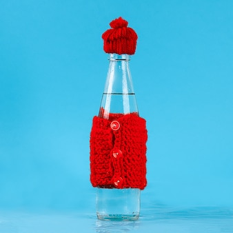 冷たい水が入ったガラス瓶は帽子と暖かいジャケットを着ています。コンセプト熱と霜。