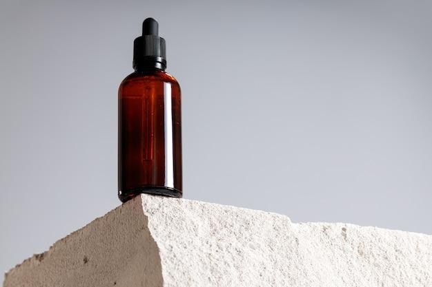 Стеклянная бутылка с косметическим маслом на сером шлакоблоке