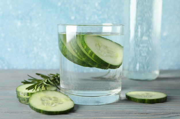 Glass and bottle with cucumber water and slices on wooden table