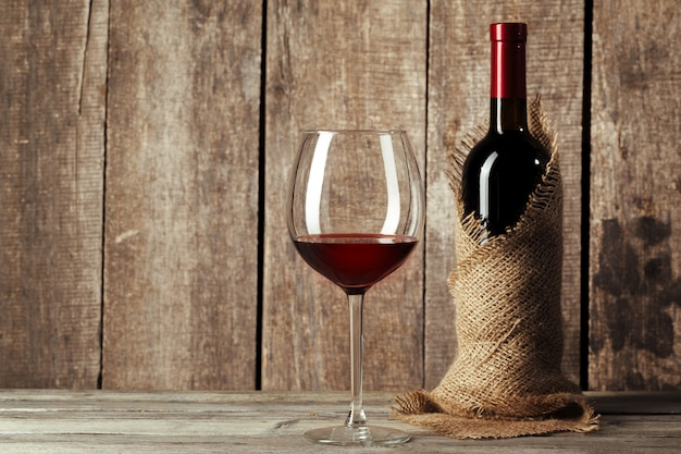 Glass and bottle with delicious red wine on table against wood