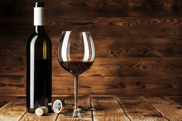Glass and bottle with delicious red wine on table against wooden wall