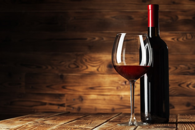 Glass and bottle with delicious red wine on table against wooden