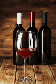 Glass and bottle with delicious red wine on table