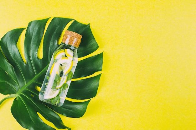 Glass bottle with detox lemonade on a monstera leaf.