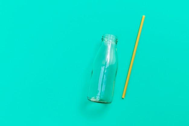 Стеклянная бутылка с экологически чистой соломкой для макарон на зеленом фоновом изображении с видом сверху копией пространства