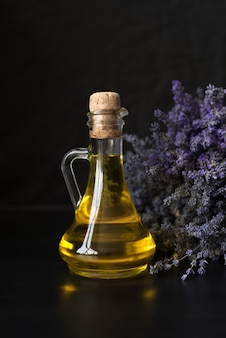 Glass bottle with fragrant lavender oil on the of a purple bouquet.