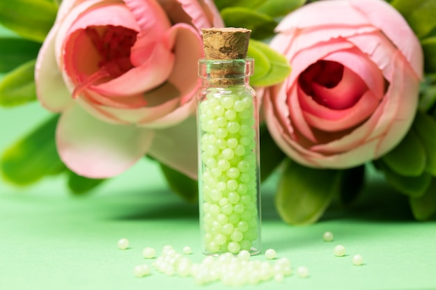 背景に緑の顆粒とバラのガラス瓶。ホメオパシー療法