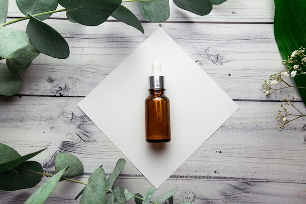 A glass bottle with hyaluronic serum lies on a white square on a wooden background surrounded by eucalyptus branches and plants cosmetology product