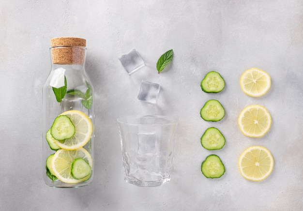 Glass bottle with infused water with lemon, cucumber, mint, ice