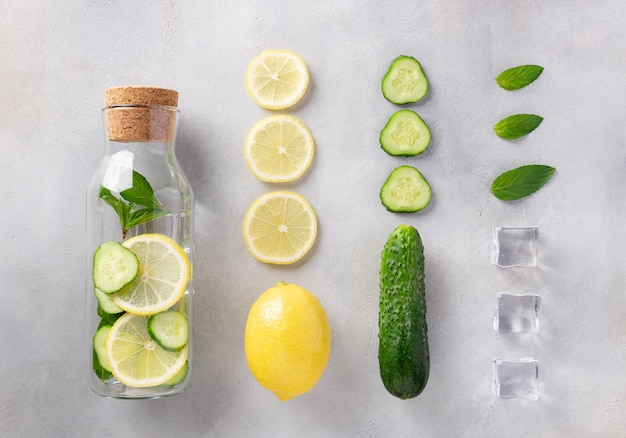 Glass bottle with infused water with lemon, cucumber, mint and ice