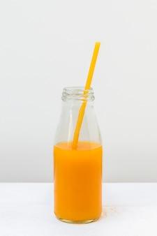 Стеклянная бутылка с соком и макаронами соломой на светлом фоне вертикальное изображение безотходной концепции жизни