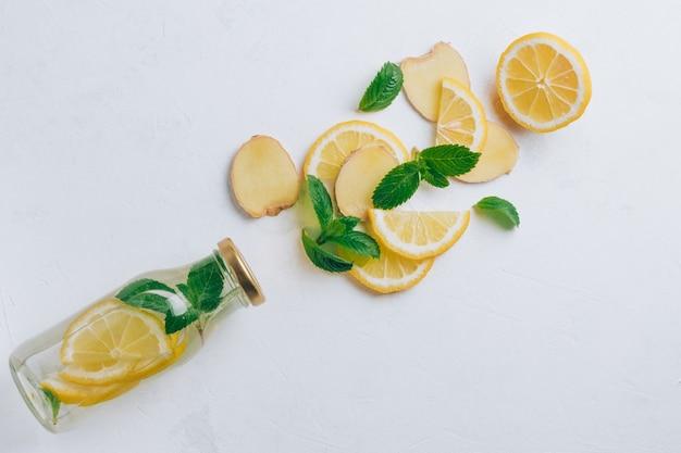 Стеклянная бутылка с лимонадом и ингредиентами для приготовления. имбирь, лимон, мята на белой поверхности. плоская планировка. вид сверху