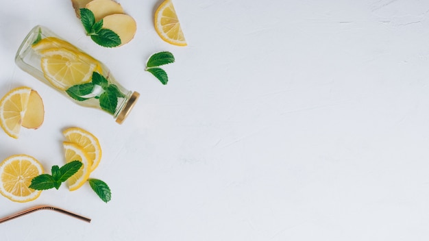Glass bottle with lemonade and metal straw. ginger, lemon, mint on white surface. flat lay, top view. copy space. banner