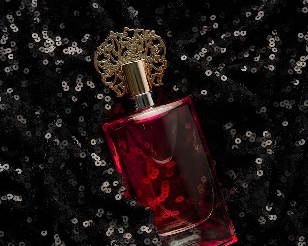 Стеклянная бутылка с розовой парфюмерной жидкостью на черном фоне с блестящими блестками