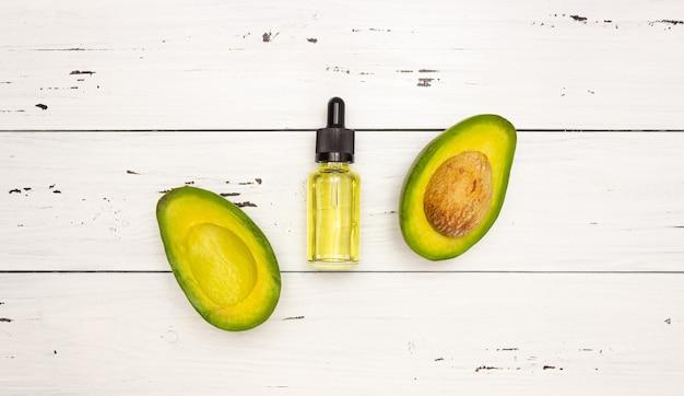 피펫과 아보카도 오일과 밝은 나무 배경, 평면도에 아보카도 과일 유리 병. 얼굴과 몸의 피부 관리와 건강한 영양.